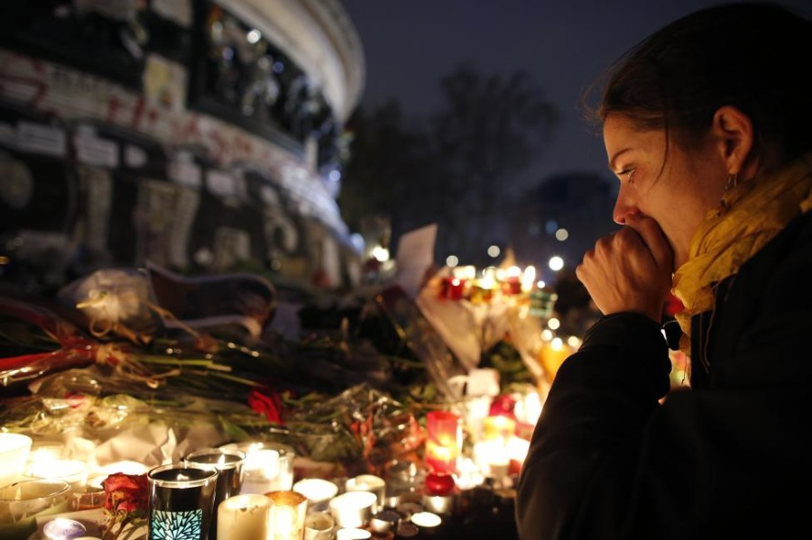 A woman weeps as she kneels near bouquets of flowers and burning candles at the Place de la Republique in Paris, France, November 16, 2015, as people continue to pay tribute to the victims of the series of deadly attacks in the French capital on Friday. REUTERS/Christian Hartmann