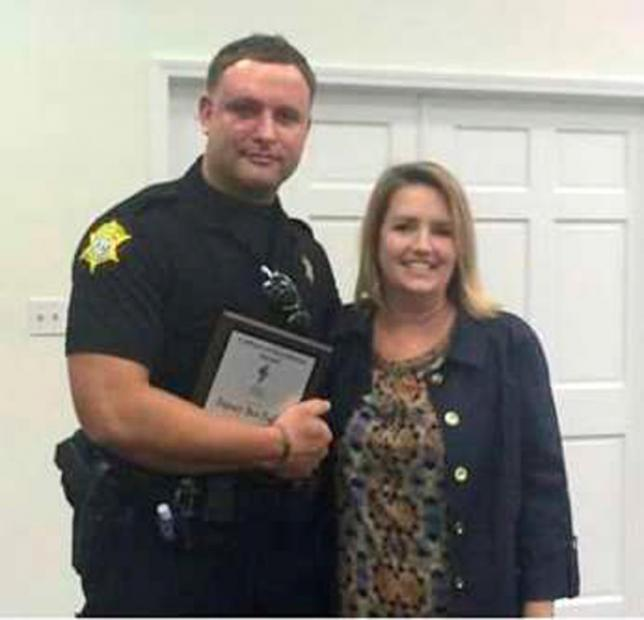 Richland County Sheriffs Department Officer Senior Deputy Ben Fields is pictured with Karen Beaman (R), Principal of Lonnie B. Nelson Elementary School after receiving Culture of Excellence Award at Lonnie B. Nelson Elementary School in Columbia, South Carolina on November 12, 2014.  REUTERS/Richland County Sheriffs Department/Handout
