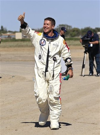 Felix Baumgartner, of Austria, gives a thumbs up to Mission Control staff, family, and friends after successfully jumping from a space capsule lifted by a helium balloon at a height of just over 128,000 feet above the Earth's surface, Sunday, Oct. 14, 2012, in Roswell, N.M.