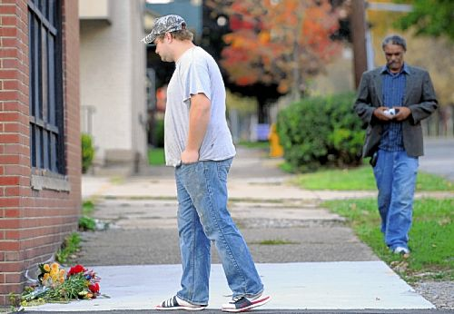 A friend of slain Washington and Jefferson football player Tim McNerney pauses Thursday at the scene of the killing across the street from campus.